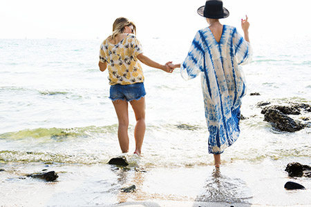 Two women on a beach holding hands
